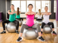 Fitness sport and lifestyle concept - three pregnant women with exercise balls in gym.